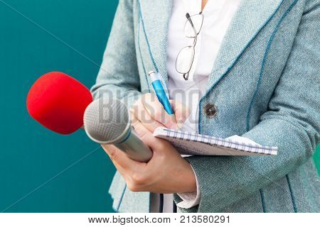 Female journalist at press conference writing notes, holding microphones