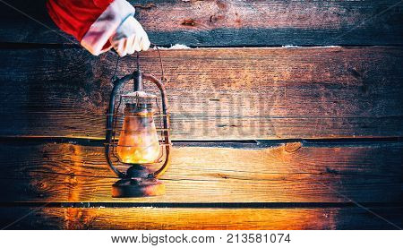 Santa Claus hand holding vintage oil lamp over Christmas holiday wooden rural background. Beautiful Empty Christmas room. New Year Background. Search, searching concept.