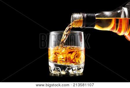 Whiskey with ice. Pouring whisky from the bottle on black background. Glass of rum alcohol close-up. Isolated on black