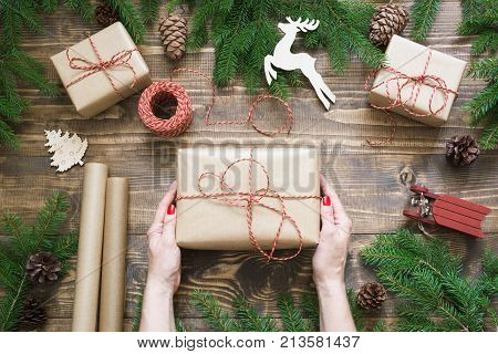 Christmas giftbox and presents wrapping in craft paper and decor on wooden board. Flat lay. Top view. Woman holding giftbox.