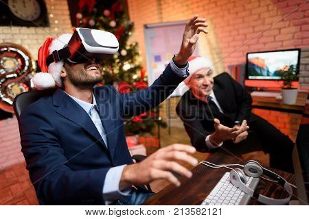 Businessman On New Year's Eve In The Office. It Has A Virtual Reality Helmet. He Plays The Game.