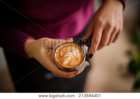 Woman in a purple shirt holding a temper with a beautiful latte art. Coffee concept
