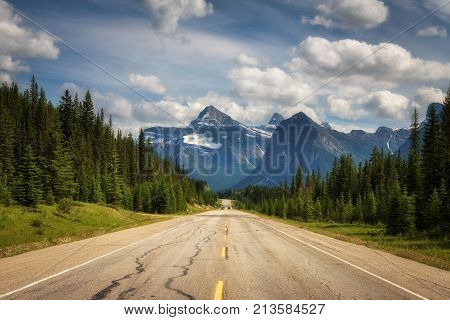 Scenic view of the road and canadian rockies on Icefields Parkway. It travels through Banff and Jasper National Parks and offers spectacular views of the Rocky mountains.