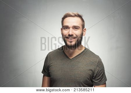 Dark-haired brown-eyed handsome man, smiling at the camera, looking chill. Casual portrait