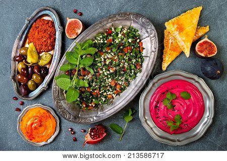 Middle Eastern traditional dinner. Authentic arab cuisine. Tabbouleh sambusek muhammara pumpkin and beet hummus. Top view flat lay overhead