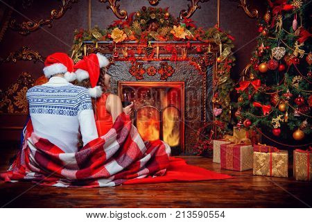 A loving couple celebrating Christmas in a cozy atmosphere by the fireplace and Christmas tree. Love, Christmas and New Year concept.