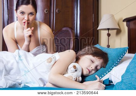 Close Up Mom And Daughter In Bedroom. Mother Showing Hash Sign At Camera, Daughter Closed Eyes And S