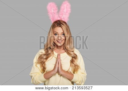 Please! Attractive young woman in pink bunny ears keeping hands clasped and looking at camera while standing against grey background