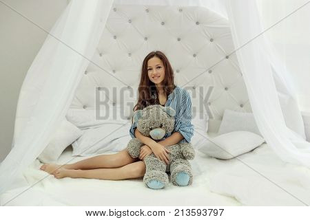 teen girl sitting on white round bed in bedroom and hugs teddy bear