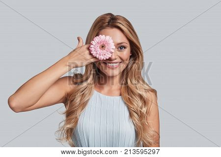Perfect as a flower. Attractive young smiling woman covering eye with a flower and looking at camera while standing against grey background