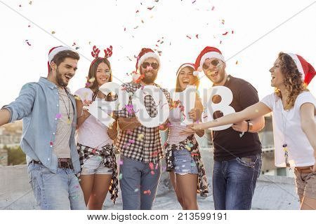 Group of young friends celebrating New Year dancing singing and having fun at a building rooftop party