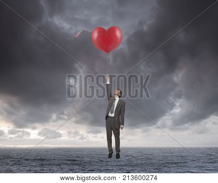 young businessman flying over the sea with heart shaped balloons