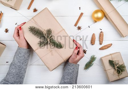 Woman with red manicure holding Christmas present wrapped in kraft paper on white wooden table background free space. Close up of gift box in girl's hand. Christmas background. Flat lay top view
