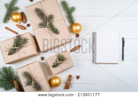Top view of blank notebook for template design on white wooden background with xmas decorations copy space. Christmas background with notebook for wish list or to do list and gift boxes. Flat lay