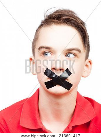 Portrait of teenager boy with duct tape on his mouth - silenced child concept