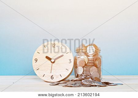 Business, savings time, time is money, deadline or delay concept : wooden alarm clock and coins on white background