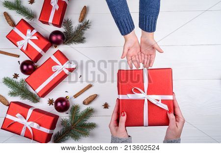 Mother giving christmas gift to son top view. Holidays present childhood and happiness concept. Close up of child and mother hands with gift box on white background. Christmas family traditions