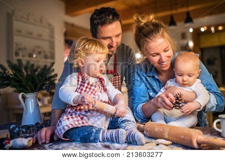 Beautiful young family making cookies at home. Father, mother, toddler boy and baby having fun.