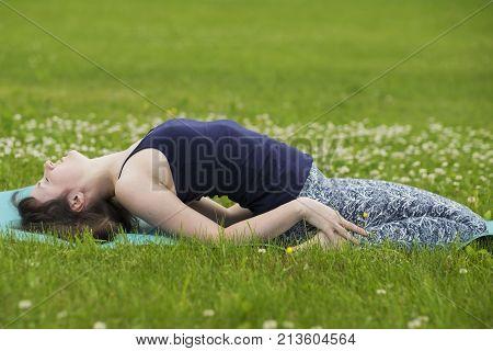Thin girl doing yoga outside at summer on green grass. Fish pose matyasana