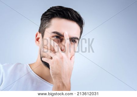 Hiding face. Mysterious serious young person looking weird while standing and closing half of his face with a hand
