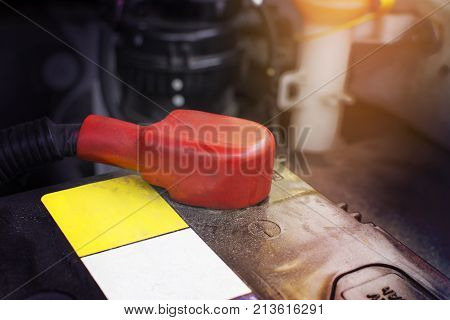 Battery anode terminal with red rubber cover is installed on a black battery in a electric system of car engine. Automotive parts concept.