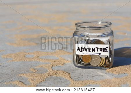 Glass jar with coins for adventure on gray floor with sand background, copy space. Money box, distribution of cash savings concept.