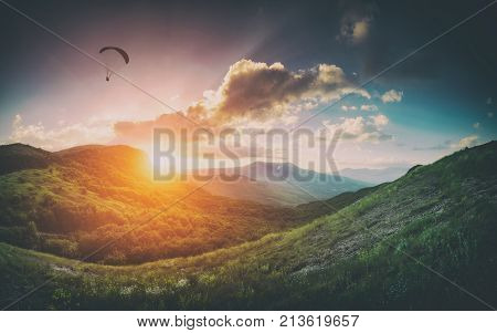 Paraglider silhouette in a light of sunset over the mountain valley. Instagram vintage stylisation.