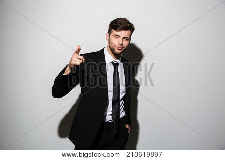 Young smiling guy in formal wear with hand in his pocket pointing with finger on you, looking at camera, isolated on white background