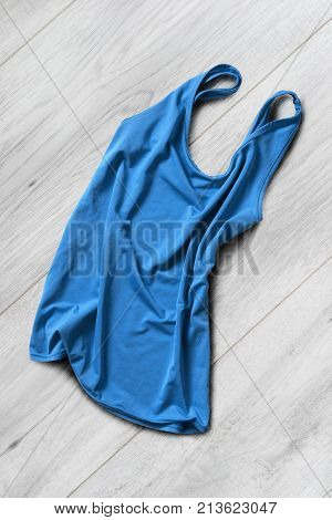 Crumpled blue basic tank top on white wooden background