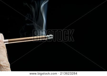 smoking brown cigarette or cigarillus in wrinkled fingers on black background closeup