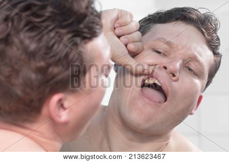 man looking in the mirror teeth . Photos in the studio