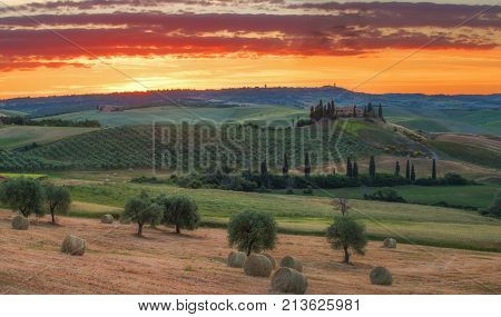 Tuscany, Italy - May 26, 2017: Magnificent spring landscape at sunrise.Beautiful view of typical tuscan farm house, green wave hills, cypresses trees, hay bales, olive trees, beautiful golden fields and meadows.