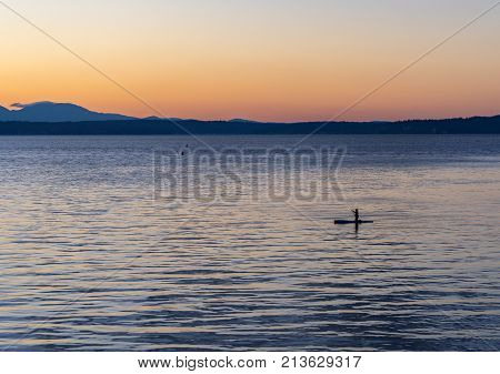 A woman kneels on her paddleboard during the sunset on Puget Sound near Seattle