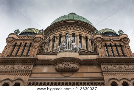 Sydney Australia - March 25 2017: Entrance facade of historic Victoria shopping mall on York Street shows three domes and a frieze with statues of human beings under heave sky.