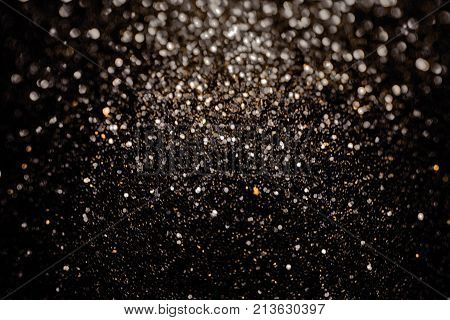 Black glitter sparkle background with gold inclusion. Black friday shiny pattern with sequins. Christmas glamour luxury pattern, black christmas and glitter diamond background. Dark silver black friday pattern