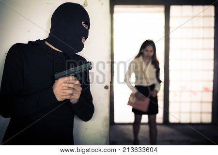 Robber Holding Up And Waiting Woman To Steal Her Wallet Or Hand Bag By Hand Gun In Corner Of Buildin