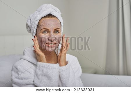 Woman at a spa having a face mask beauty treatment wearing white towelling robe and headdress smiling at the camera