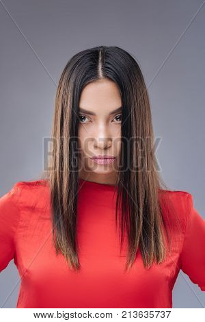 Spoilt person. Young beautiful selfish woman standing against the blue background and frowning while being offended