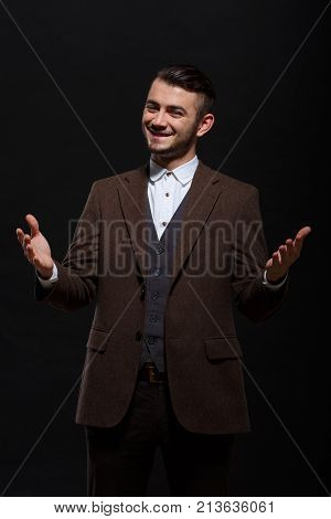 A fashionable guy with a smile and a stylish hairdo spread his arms, shows that he is happy to be seen on a black background