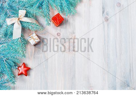 Festive Christmas background. Christmas toys blue fir tree branches on the wooden background. Christmas still life with free space for text. Christmas background with blue fir tree branches and Christmas toys
