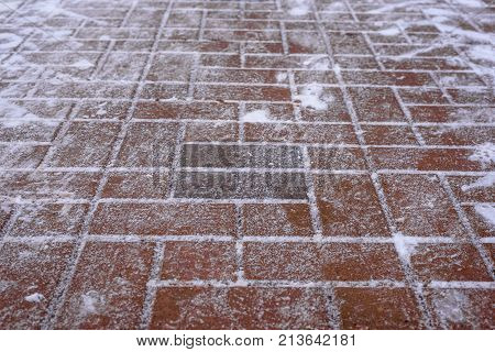 Horizontal shot of paving slabs of red-brown color, covered with snow close up