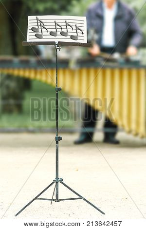 Vertical shot of music stand with notes close-up on blur background of the musician playing on xylophone on the street.