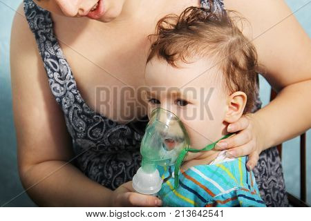 Little Cute Girl Doing Inhalation At Home. Two Year Old Baby Inhaling From The Inhaler, Mother Holdi