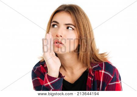 Image of young woman standing isolated over white wall background. Looking aside talking with you gossiping.