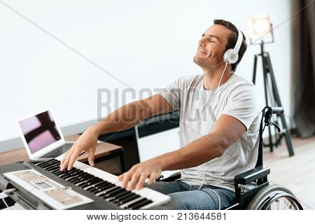 The disabled person is sitting in a wheelchair in front of the synthesizer. He plays music. He is in his large bright living room. He enjoys music.
