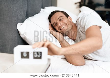 The disabled person sleeps in his white bed. There is an alarm clock in front of him. He smiles and pulls him off. He is in the bedroom of his modern apartment. The man is sleeping in a white T-shirt.