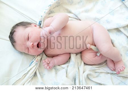 Infant baby with umbilical cord first day of life lying on drapery sheets
