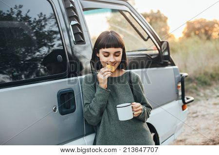 Cute young attractive female tourist drinks coffee or hot tea during rest stop in forest on hiking trip on road leans on camper van and snacks on tasty cookie concept camping and travel cup mockup