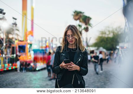 Trendy fashion teenager or young woman uses communication technology or messaging application to keep in touch or meetup with friends on smartphone in middle of crowd at amusement park or festival concept social media influencer