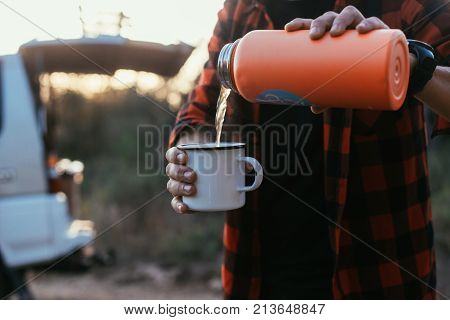 Close up of man or woman pouring hot liquid of tea or coffee from thermos flask into the aluminium mug during summer evening in camping site or during hiking trip stands in front of caravan van